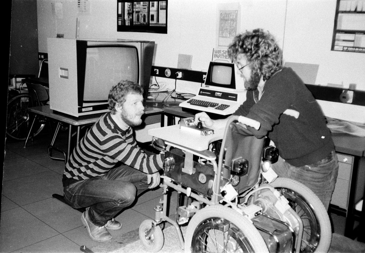 """April 1982: Die Diplomanden des Fachbereichs Elektrotechnik Helmut Holtkamp und Leonhard Jiresch entwickeln ein Rollstuhl-Trainingsgerät für Schwerbehinderte, mit dem man Rollstuhlfahren auf kleinstem Raum lernen kann. """"Damals mussten Behinderte in einer Turnhalle den Umgang mit dem elektrischen Rollstuhl lernen"""", erinnert sich Helmut Holtkamp. """"Es gab dann die Idee, dass man dafür doch auch einen Simulator entwickeln könnten und das haben wir dann gemacht."""" Das Gestell für den Rollstuhl bekamen die beiden"""