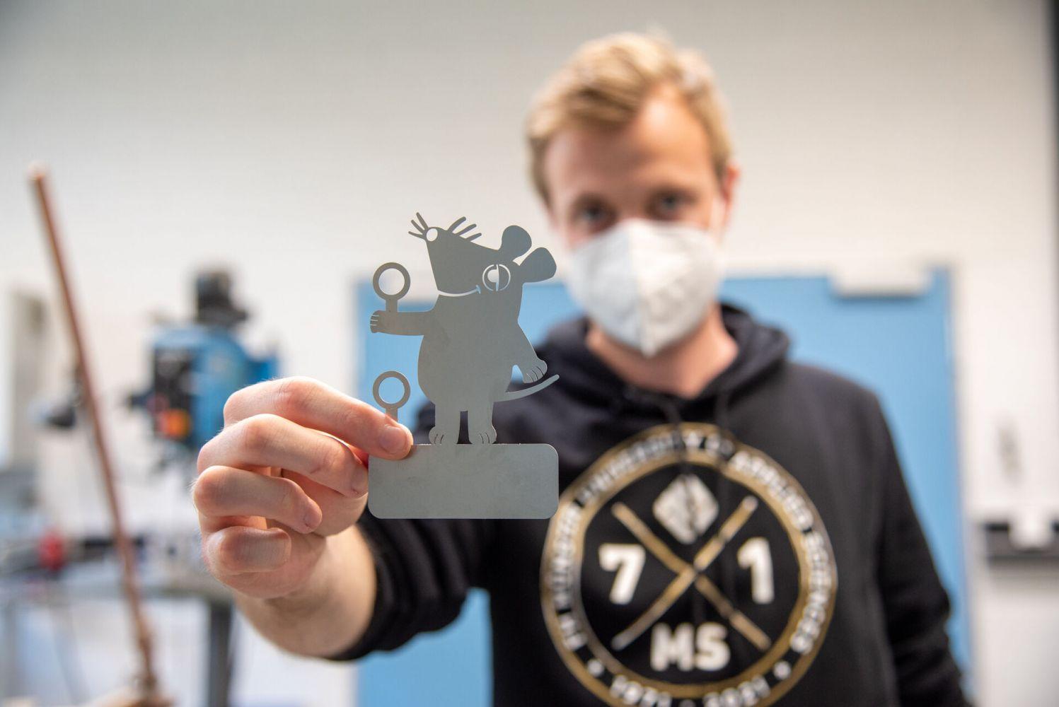 Mitarbeiter des Laserzentrums hält eine Maus aus Metall ins Bild.