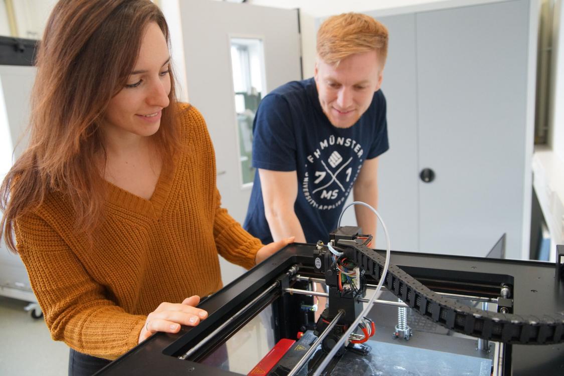 Studierende an einem 3D-Drucker