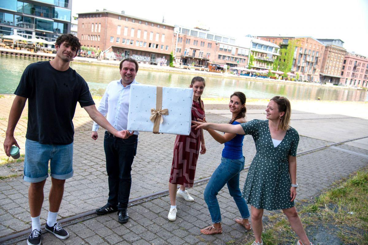 Mehrere Mitarbeitende der FH Münster mit einem großen Geschenk (Foto: FH Münster/Katharina Kipp )