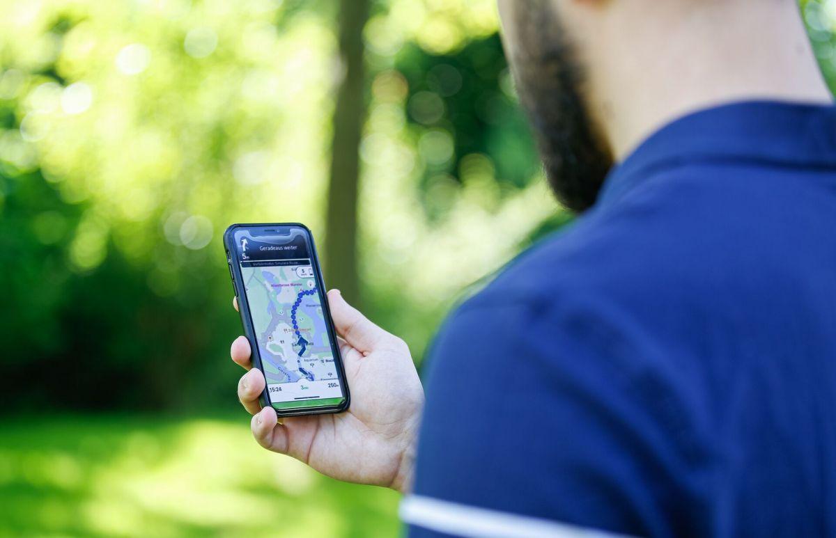 Ein Mann schaut auf sein Handy. Darauf ist die Navigations-App für den Zoo zu sehen.