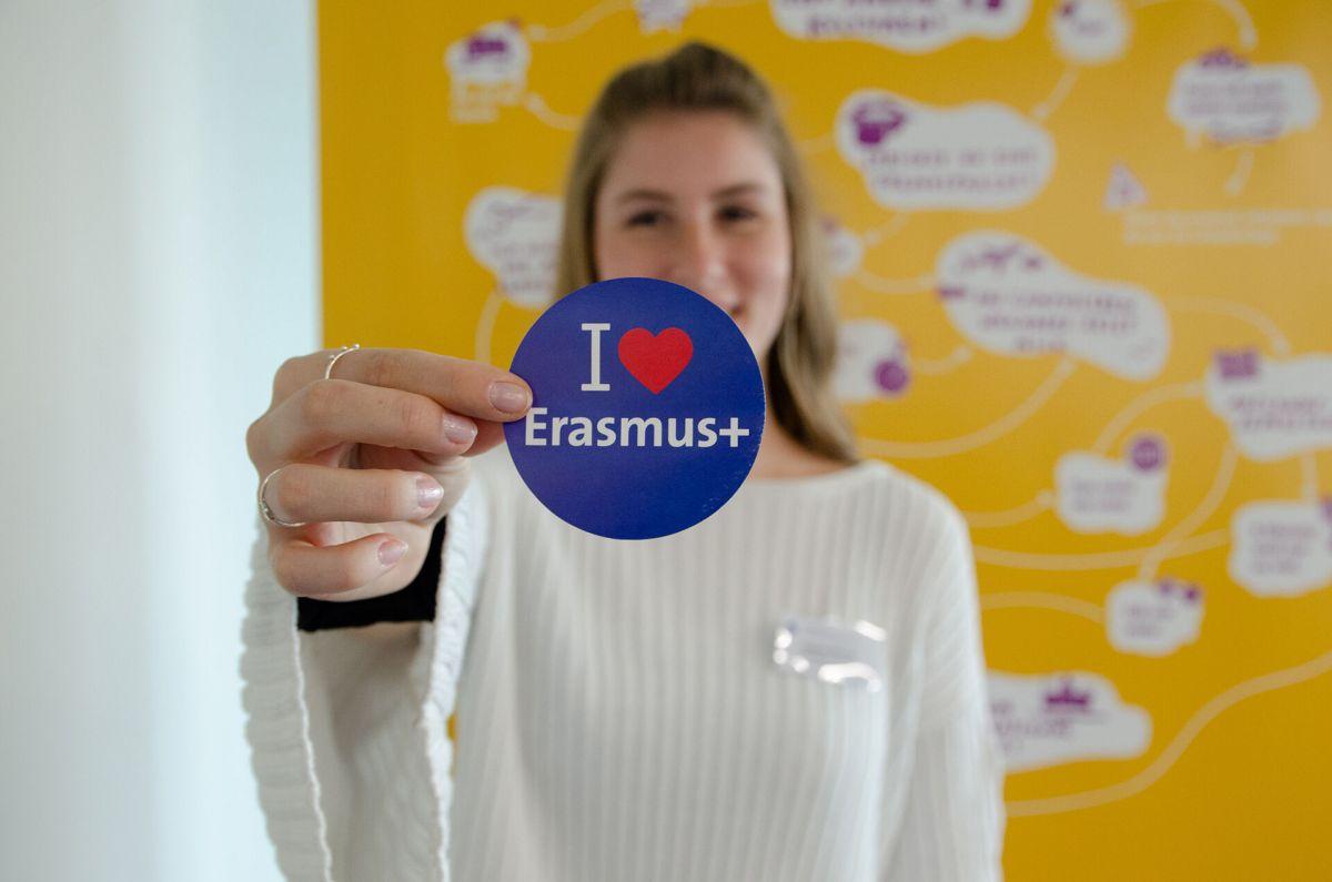 Eine Frau mit einem Sticker in der Hand. Auf ihm steht I Love Erasmus.
