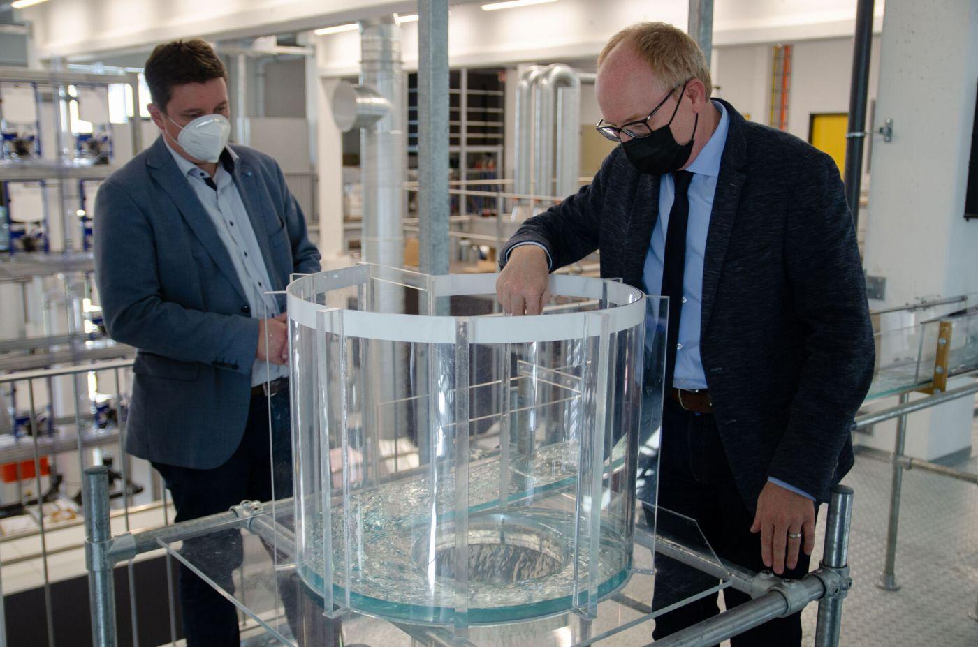Zwei Männer stehen in einem Labor und schauen in einen Schacht mit Wasser. (Foto: FH Münster/Frederik Tebbe)