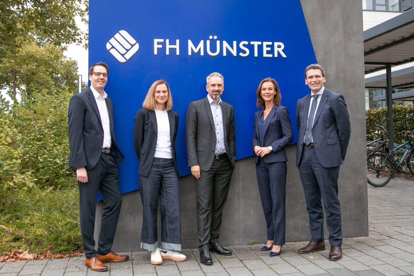 Eine Gruppe steht vor dem Logo der FH Münster.