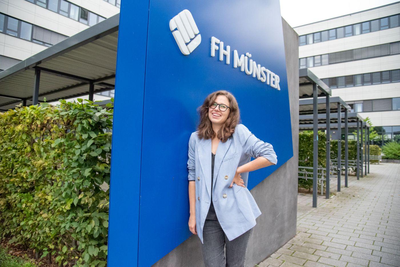 Polina Voitenko steht draußem am Fachhochschulzentrum neben dem blauen FH-Logo.  (Foto: FH Münster/Katharina Kipp )