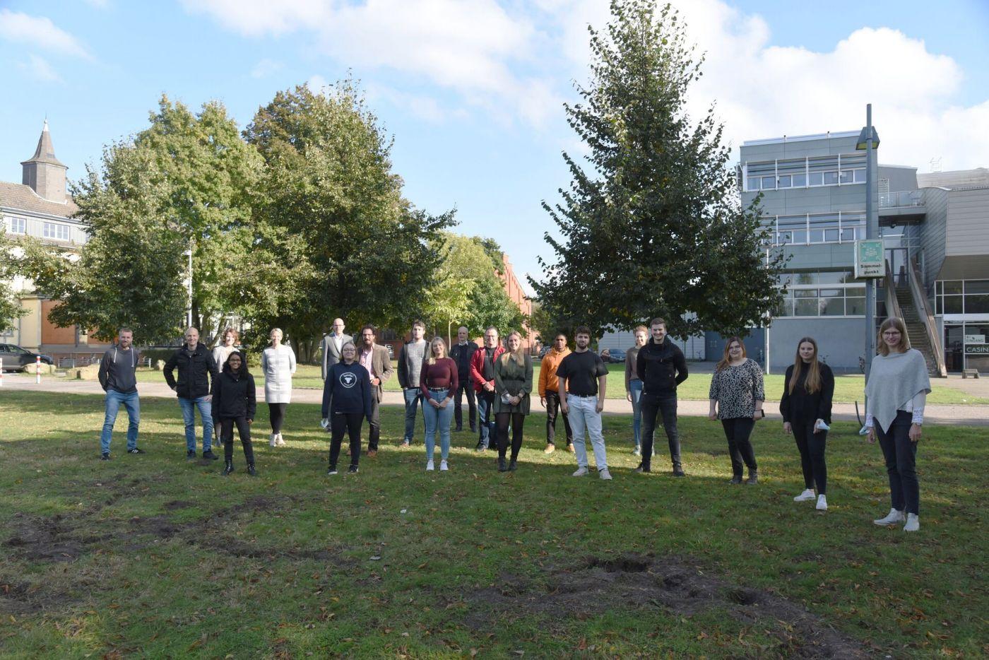Eine Gruppe Menschen steht auf dem Rasen. (Foto: FH Münster/Pressestelle)