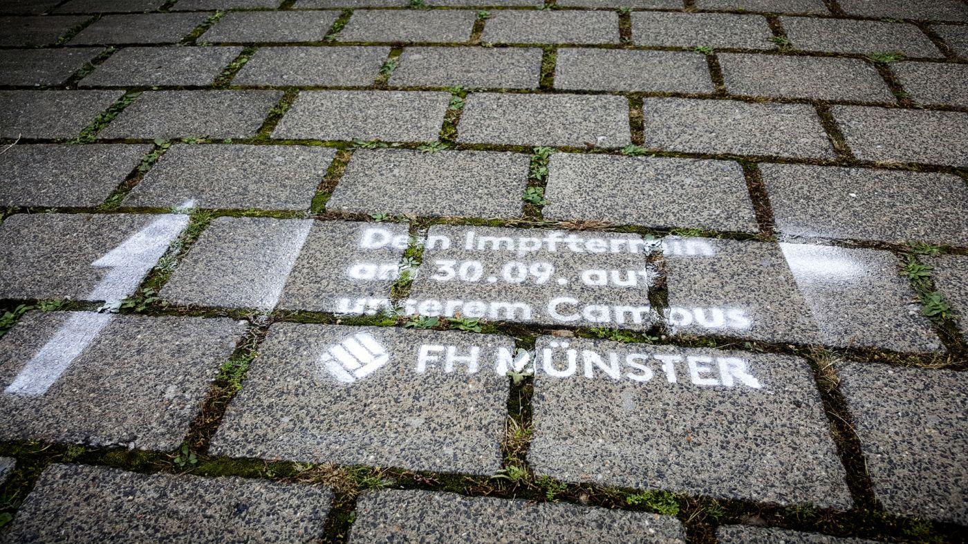 """Ein mit Kreidespray auf den Boden gesprühter Text mit den Worten """"Dein Impftermin am 30.09. auf unserem Campus - FH Münster"""""""