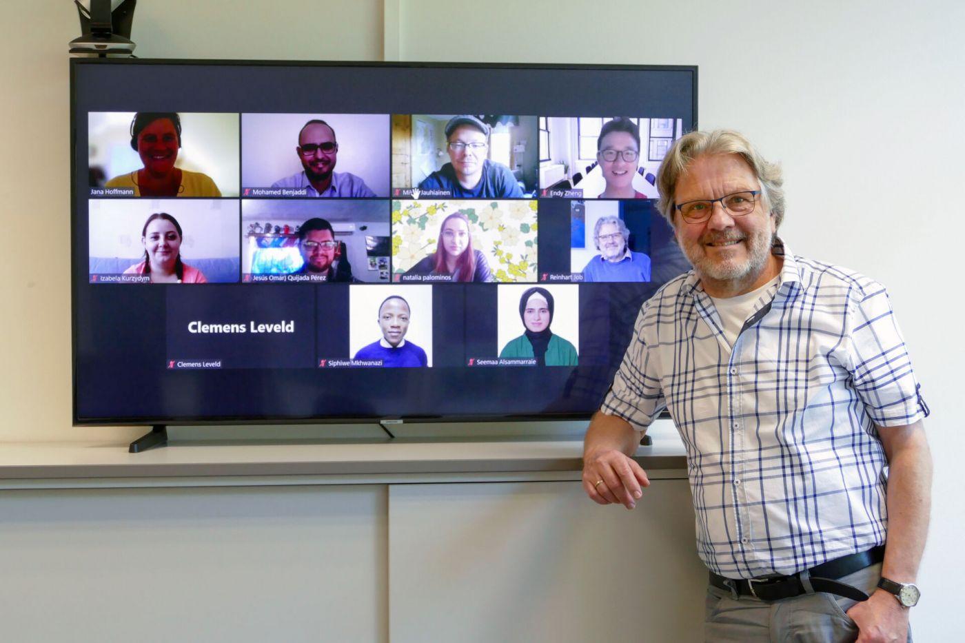 Prof. Dr. Reinhart Job steht neben einem Fernsehbildschirm, auf dem mehrere Videokacheln mit den Köpfen der Teilnehmerinnen und Teilnehmer einer Videokonferenz zu sehen sind.  (Foto: FH Münster/Jana Schiller)