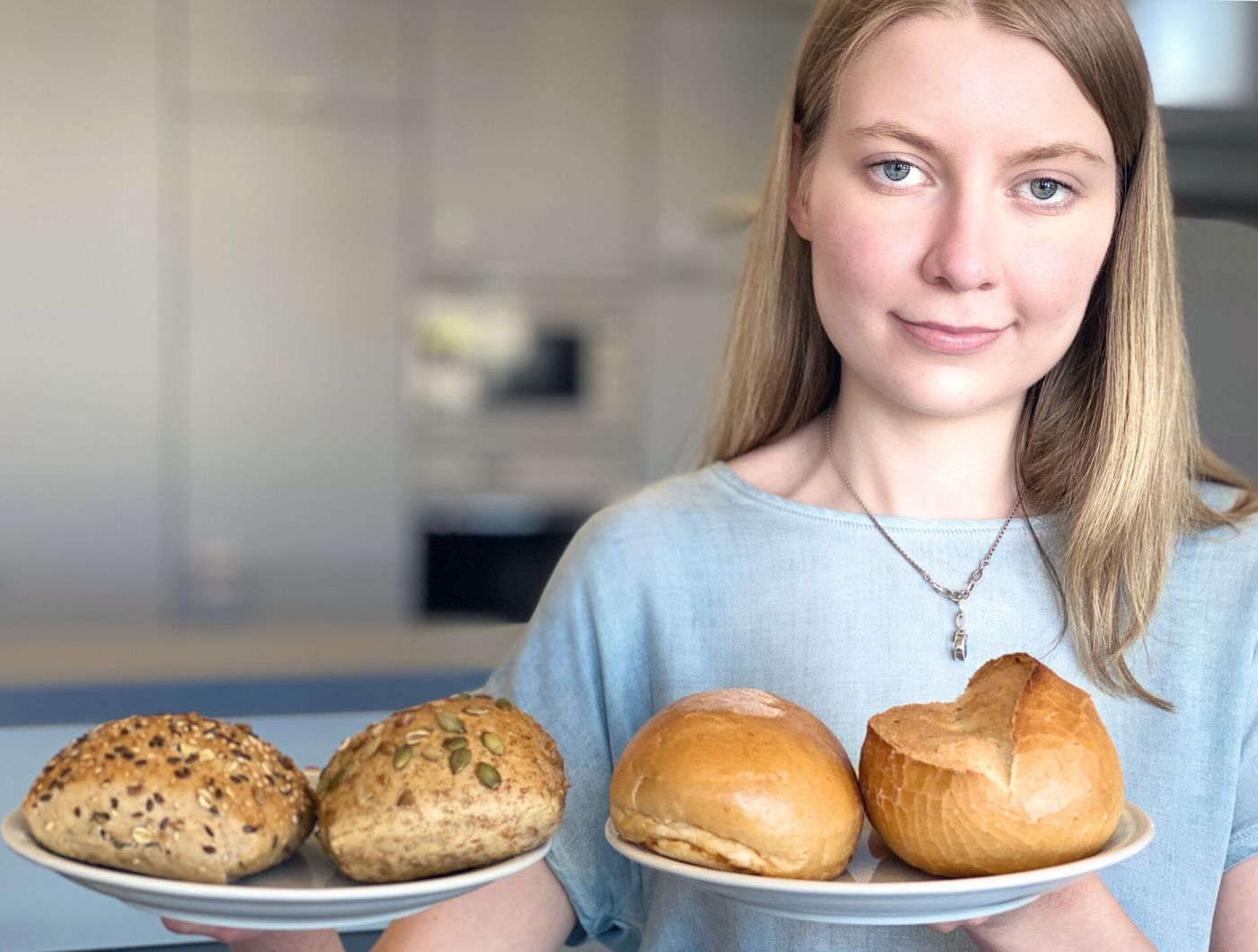 Eine junge Frau hält zwei Teller ins Bild. Links sind Vollkorn-, rechts Weizenbrötchen.