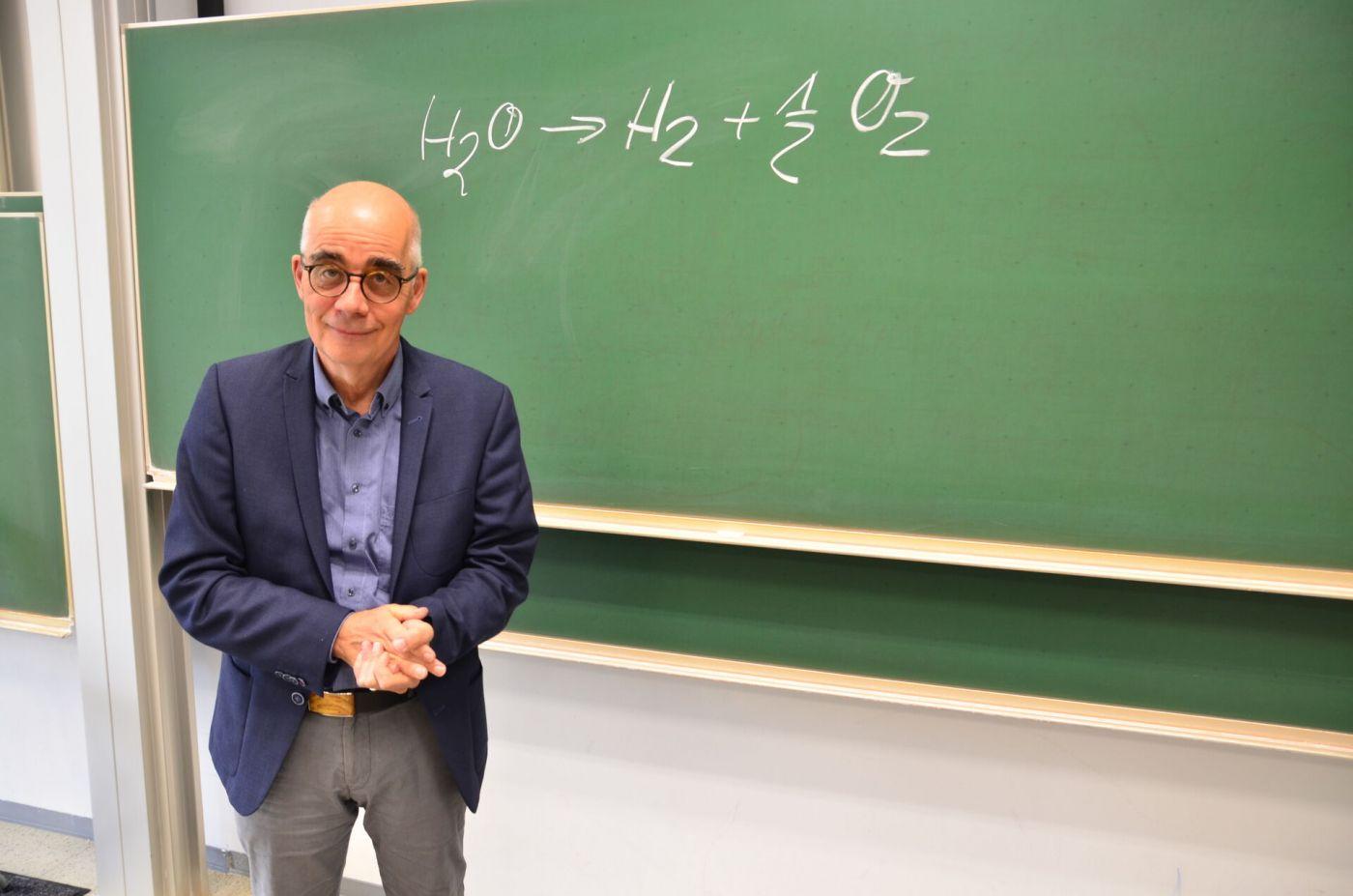 Ein Professor steht im Hörsaal vor einer Tafel.