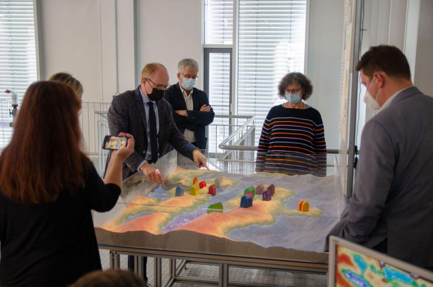 Sechs Personen stehen vor einer Sandbox mit Augmented Reality Technik. (Foto: FH Münster/Frederik Tebbe)