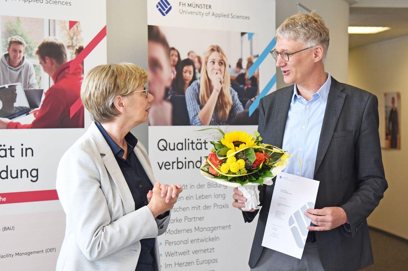 Prof. Dr. Ute von Lojewski und Prof. Dr. Hugo Mennemann mit Blumenstrauß und Jubiläumsurkunde