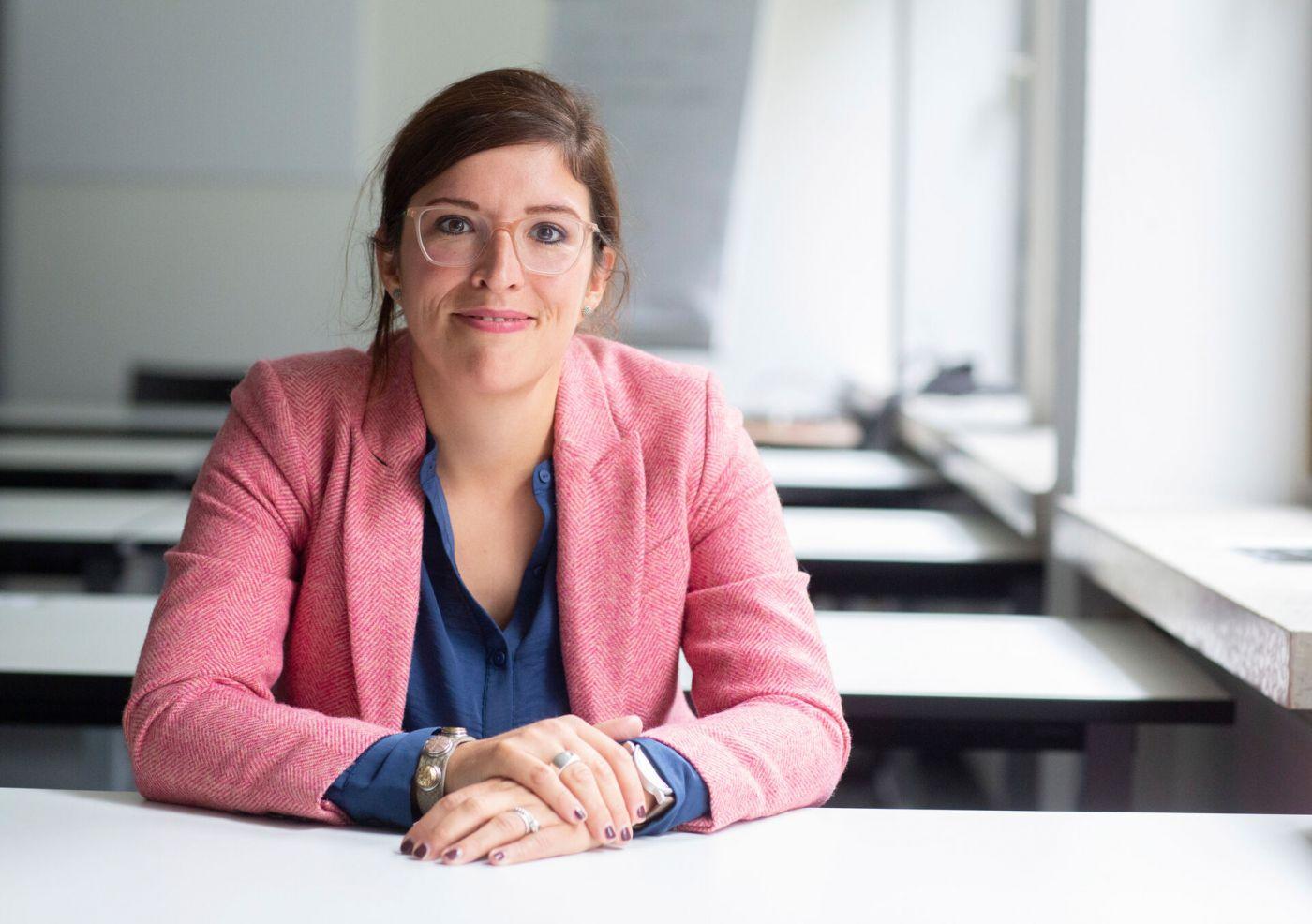 Prof. Dr. Laura Best vom Fachbereich Sozialwesen der FH Münster sitzt an einem Tisch.