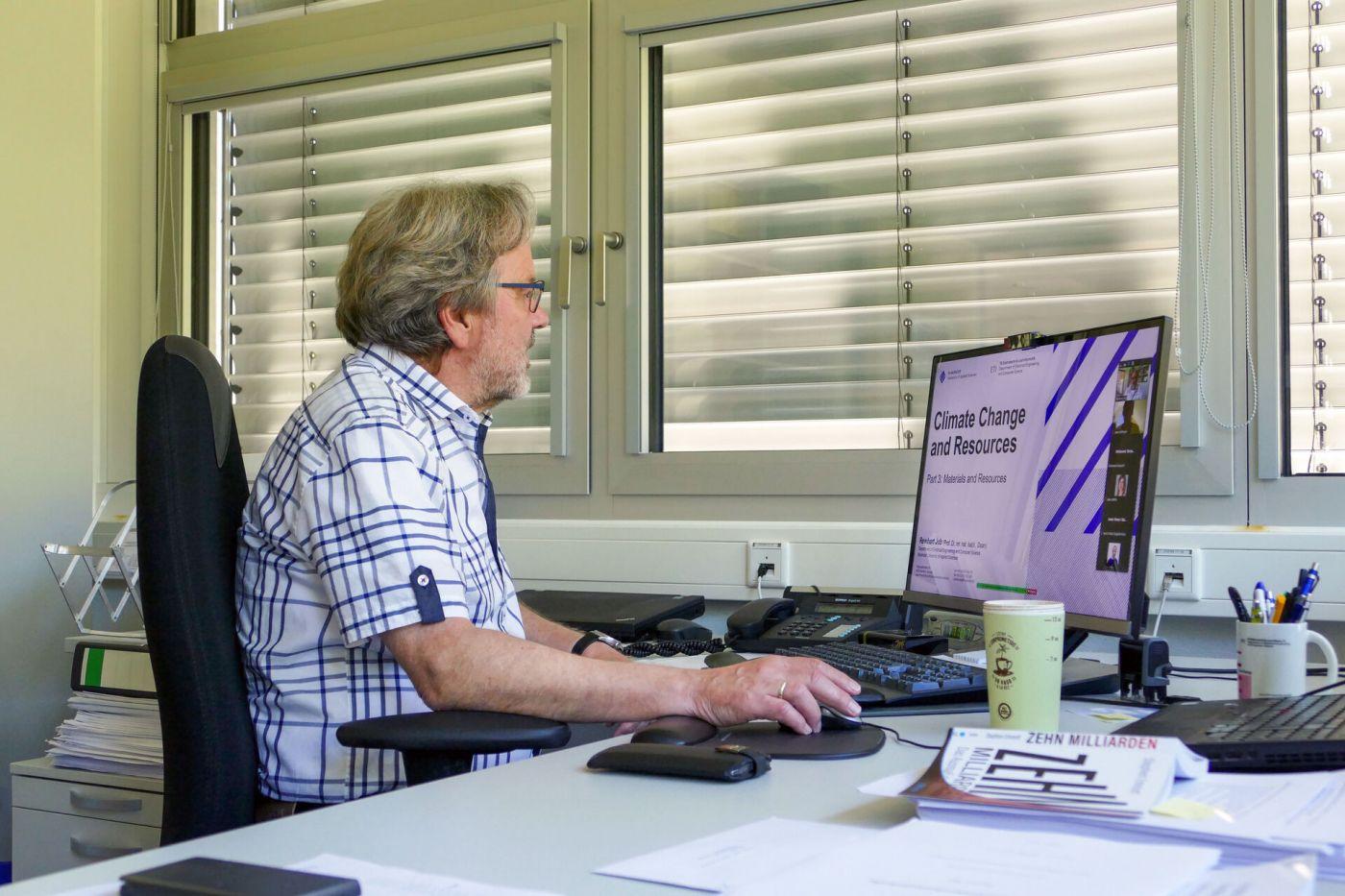 Prof. Dr. Reinhart Job sitzt am Schreibtisch vor dem Computerbildschirm, auf dem die Präsentation seiner Online-Vorlesung über Klimawandel und Ressourcen zu sehen ist.  (Foto: FH Münster/Jana Schiller)