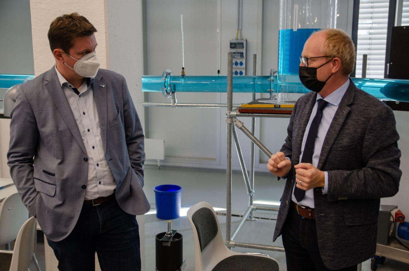 Zwei Männer unterhalten sich in einem Labor. Im Hintergrund befindet sich ein mit Wasser gefülltes Rohrsystem. (Foto: FH Münster/Frederik Tebbe)