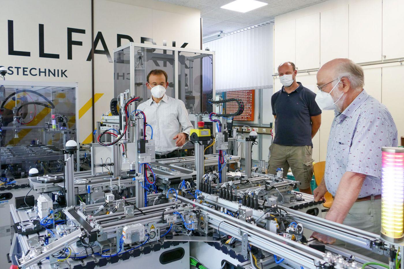 Prof. Dr. Falk Saleweski zeigt Prof. Dr. Rainer Schmidt die neue Modellfabrik. Zwischen ihnen steht Hendrik Kösters. (Foto: FH Münster/Jana Schiller)